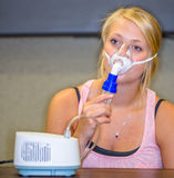 Girl using Nebulizer. A young woman using a nebulizer aerosol mask and compressor Royalty Free Stock Images