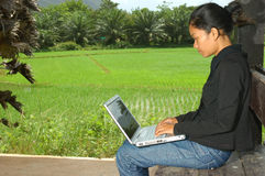 Girl Using Notebook Computer Outside. A girl using her notebook computer outside while she has some free time Royalty Free Stock Images