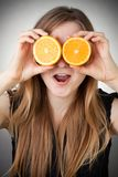 Girl using orange as eyes, with grey background Royalty Free Stock Image