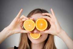 Girl using orange as eyes, with grey background Stock Photos