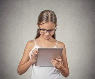 Girl using pad computer playing game. Teenager girl using pad computer playing game isolated grey background. New next generation technology concept. Student Royalty Free Stock Photo