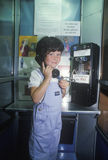 A girl using a pay telephone Royalty Free Stock Photo