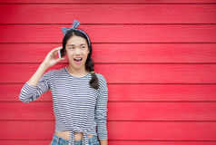 Girl using phone against wooden backdrop stock photography