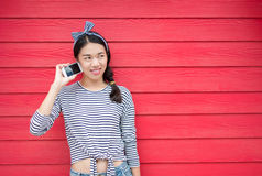 Girl using phone against wooden backdrop. Girl using phone against red wooden backdrop Royalty Free Stock Photo
