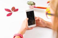 Girl using phone with broken screen. Girl using a phone with broken screen stock photos