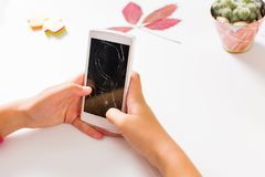 Girl using phone with broken screen. Girl using a phone with broken screen royalty free stock images