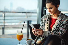 Girl using phone in a coffee shop Stock Photography