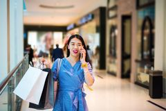 Girl using phone while doing shopping royalty free stock photos