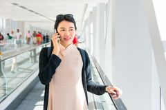 Girl using phone while on the travelator inside Stock Image