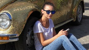 Girl using a phone next to a car stock video footage