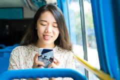 Girl using phone on public bus Stock Photo