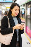 Girl using phone while waiting for the metro. At subway station Royalty Free Stock Photography