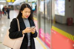 Girl using phone while waiting for the metro. At subway station Royalty Free Stock Photo