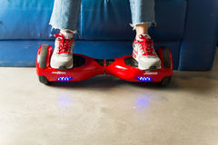 Girl using a red self-balancing two-wheeled board. The gyroscope based dual wheel electric s Royalty Free Stock Photo