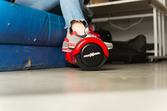 Girl using a red self-balancing two-wheeled board. The gyroscope based dual wheel electric s Stock Photos