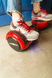 Girl using a red self-balancing two-wheeled board. The gyroscope based dual wheel electric s Stock Image