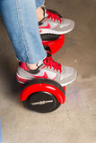 Girl using a red self-balancing two-wheeled board. The gyroscope based dual wheel electric s Royalty Free Stock Photography