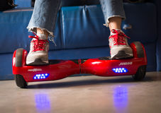 Girl using a red self-balancing two-wheeled board. The gyroscope based dual wheel electric s Royalty Free Stock Image