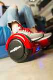 Girl using a red self-balancing two-wheeled board. The gyroscope based dual wheel electric s Stock Photography