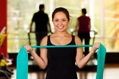 Girl using a resistance band in her exercise routine. Woman fitness elastic excercises.  Royalty Free Stock Photos