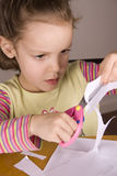 Girl using scissors Royalty Free Stock Images