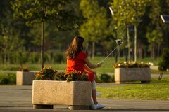 Girl using selfie stick in park Royalty Free Stock Photos
