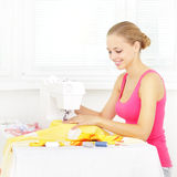 Girl using sewing machine to sew clothing Royalty Free Stock Images