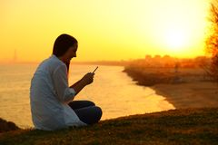 Girl using a smart phone in a beautiful sunset Stock Photography