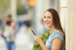 Girl using a smart phone on the street looking at you. Portrait of a happy girl using a smart phone leaning on a wall on the street looking at you royalty free stock photos