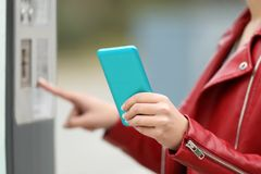 Girl using a smart phone to pay in a payment machine. Close up of a girl hands using a smart phone to pay in a payment machine outdoors Royalty Free Stock Photos