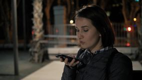Girl using smart phone voice recognition, dictates thoughts, voice dialing message at night evening street, student. Girl using smart phone voice recognition stock footage