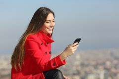 Girl using smart phone in winter with city in background. Happy girl in red using a smart phone in winter with city in background royalty free stock images