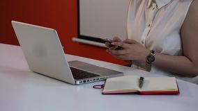 Girl using smartphone in front of laptop in the office with notebook table. Girl typing on the cell phone mobile phone smart phone in the office with note book stock video