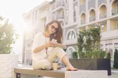 Girl using smartphone while resting on wooden bench. Smiling beautiful young woman using smartphone while resting on wooden bench in city street in summer stock photography