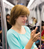 Girl  using smartphone in subway Stock Images