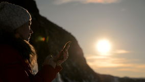 The girl is using the smartphone at sunset. Tourist girl uses a phone at sunset in the winter. The girl writes SMS text in her smartphone, communicates by video stock video