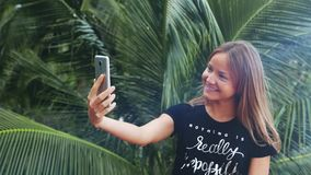 Girl using smartphone in terrace. Beautiful  young. Female professional having casual conversation on mobile phone. Jungle background stock video footage
