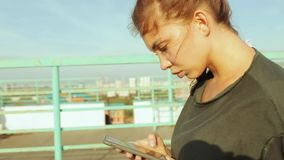 Girl using a smartphone writes sms, standing against the backdrop of the city landscape. A young girl communicates on stock video
