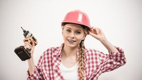 Girl using some power tools for work at home. Young woman using driil power tool for her work at home. Girl working at flat remodeling. Building, repair and stock image