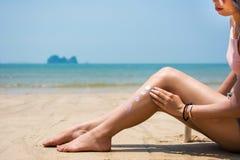 Girl using sun lotion on the beach Stock Photo