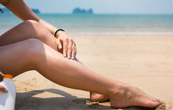 Girl using sun lotion on the beach Royalty Free Stock Image