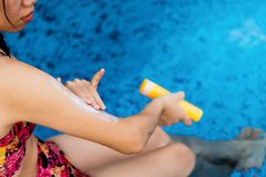 Girl using sun lotion at the pool stock photo