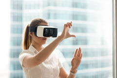 Girl using swipe and stretch gesture in VR glasses. Beautiful girl using virtual reality glasses near bright window with skyscraper view outside. Business woman Royalty Free Stock Image