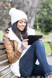 Girl using tablet computer in the park. Stock Photography