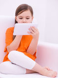 Girl using tablet. Happy little girl using tablet Royalty Free Stock Photo
