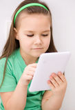 Girl using tablet. Happy little girl using tablet Royalty Free Stock Images