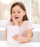 Girl using tablet. Happy little girl using tablet Royalty Free Stock Photography