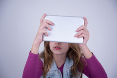 Girl using a tablet. Little Girl using a gray tablet Stock Photo