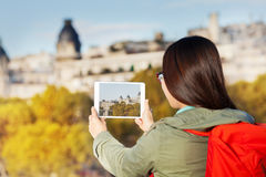 Girl using tablet making picture of autumn Paris Royalty Free Stock Image