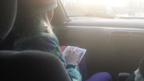 Girl using tablet PC during car travel. Young woman using tablet computer while traveling by car on front passenger seat. Sunset time stock footage